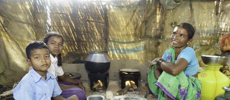 Vrouw en kinderen met kookoven in India